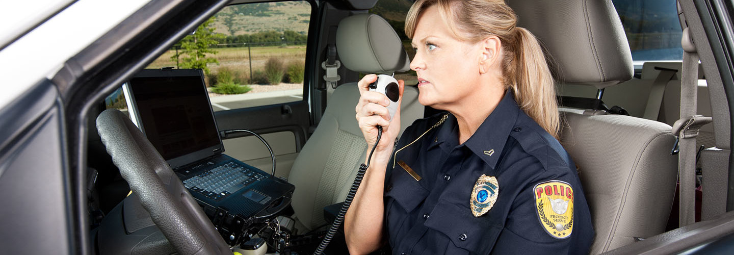Female Police Officer Talking on Radio in Vehicle