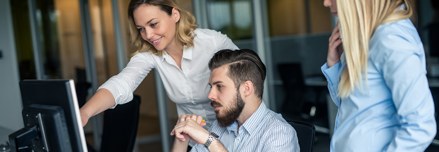 Woman training male colleague on cybersecurity at a computer screen