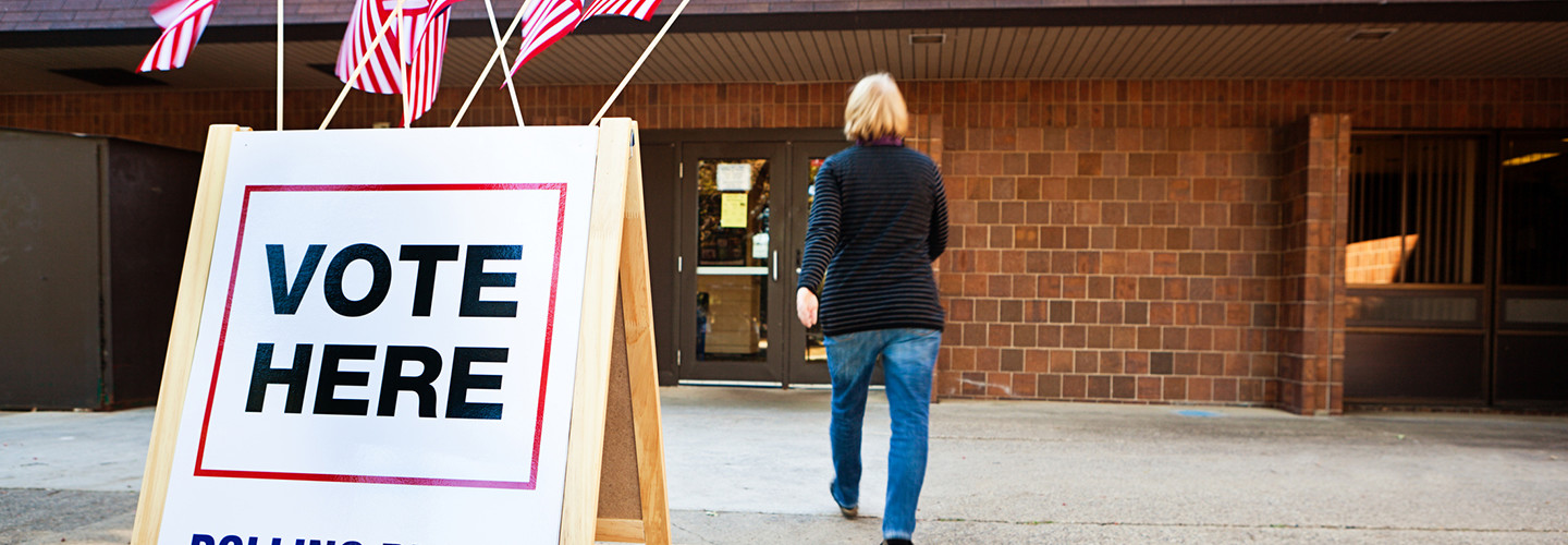 Woman walking into a polling place to vote