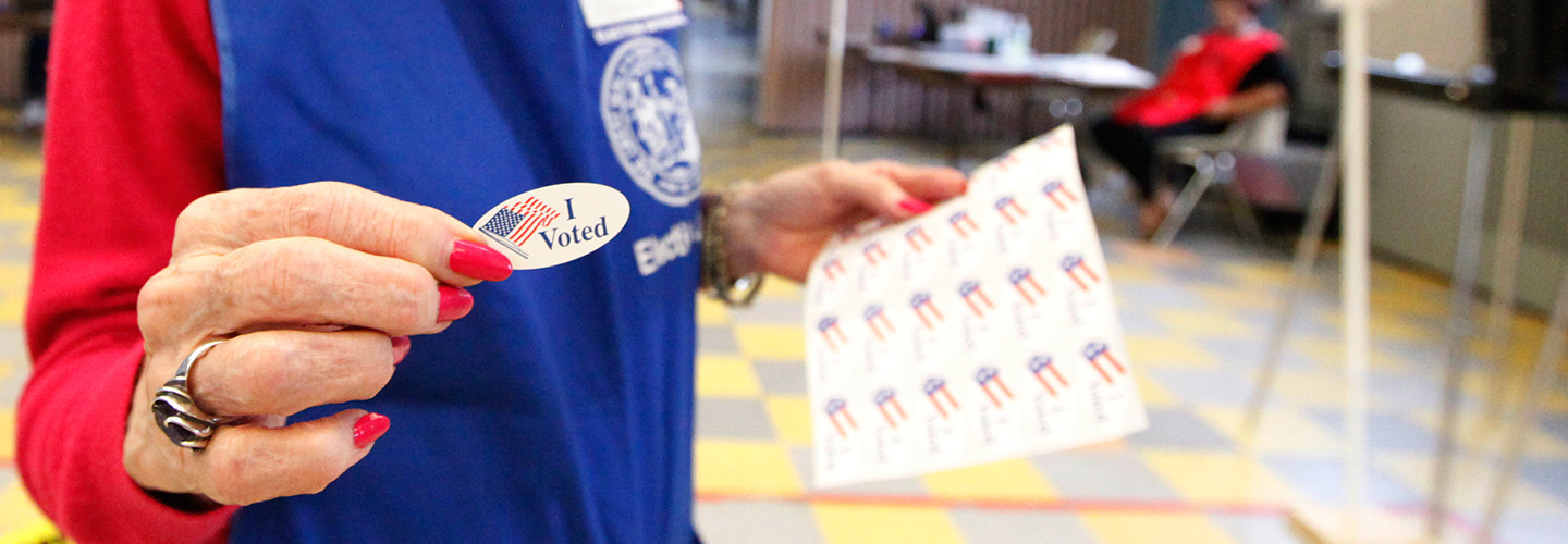 Woman handing out an I voted sticker on Election Day