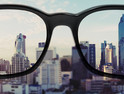 Eye glasses looking to city view, focused on glasses lens