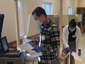 Spc. Lincoln Meverden and Pfc. Napatsawan Sanguanboon, both of the 132nd Brigade Support Battalion, process ballots May 12 in Maine, Wisconsin.