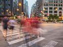 People walking across a cross-walk in Chicago at dusk