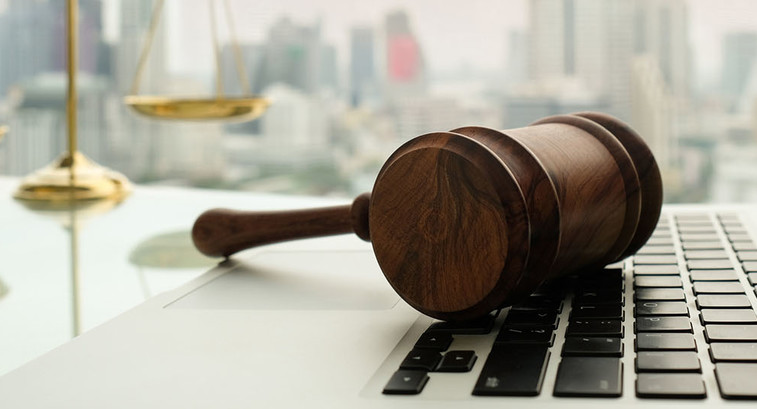 Wooden gavel on laptop keyboard with scales of justice in business city background.
