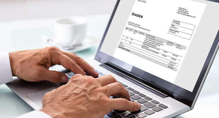 Man looking at an invoice on a laptop