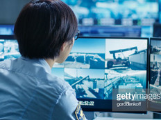 In the Security Control Room Officer Monitors Multiple Screens for Suspicious Activities.