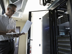 Male Caucasian IT technician using laptop in server room