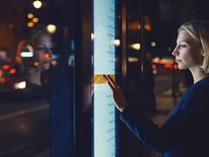 Woman using a smart touchscreen display by a bus stop in a city at night