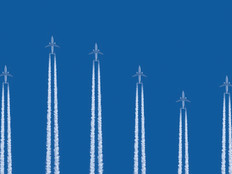 Airplanes flying vertically on a blue background with contrails below them