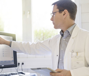 Male doctor using computer with tablet